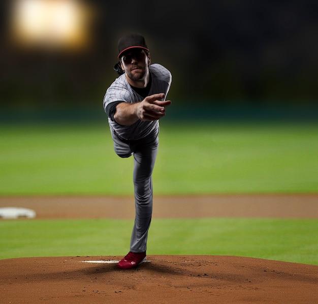Pitcher  player throwing a ball, on a baseball stadium. Free Photo