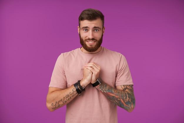 あごひげと入れ墨の哀れな魅力的なブルネットの男は、物乞いのジェスチャーで上げられた手を折りたたむ、額にしわを寄せ、広く笑って、紫で隔離 無料写真