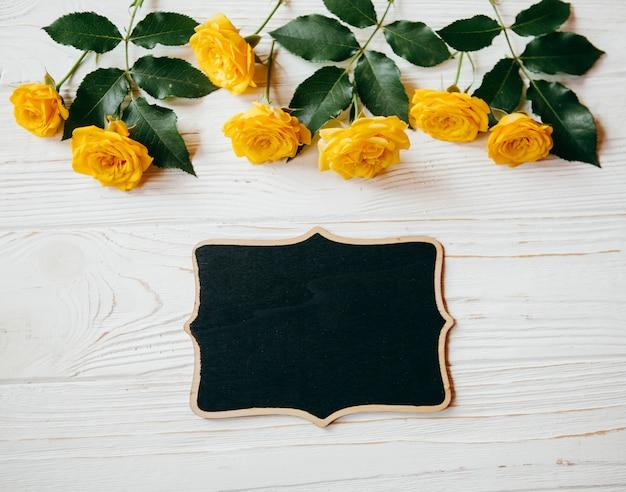 黄色いバラと白いテーブルの上のpitureフレーム Premium写真
