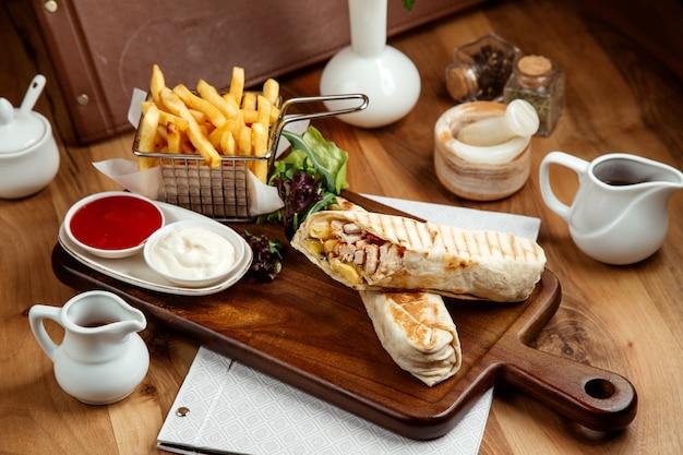 Курица шавармин pitwith картофель фри кетчуп майонез и салат на столе Бесплатные Фотографии