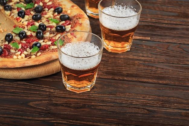 Пицца и пиво на деревянном столе в пабе, пиццерии или спорт-баре. вид сверху. Premium Фотографии