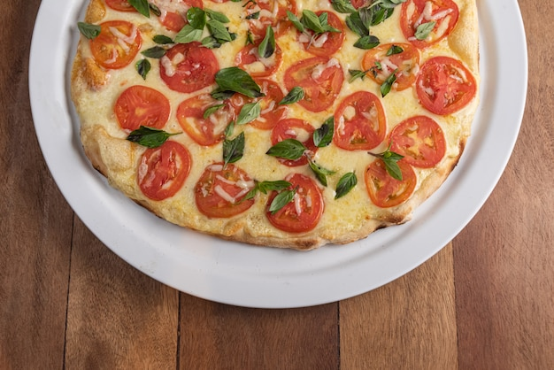 Pizza on the brown wooden table Free Photo