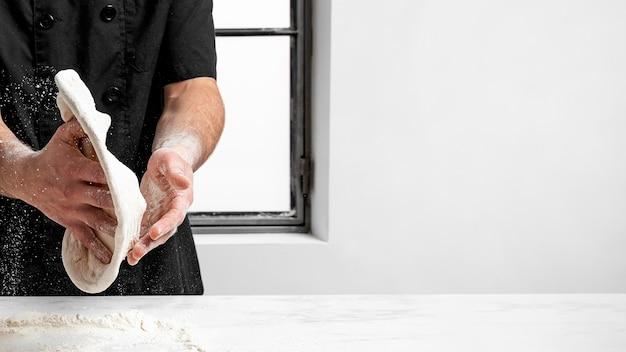 Pizzaiolo che produce pasta per pizza con copia-spazio Foto Gratuite