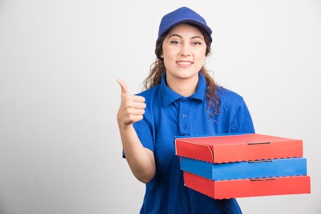 白い背景の上のピザの箱で親指を表示してピザ配達の女の子 無料写真