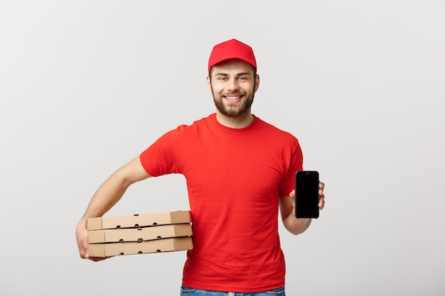 Pizza delivery man holding a mobile and pizza boxes over white background. Premium Photo