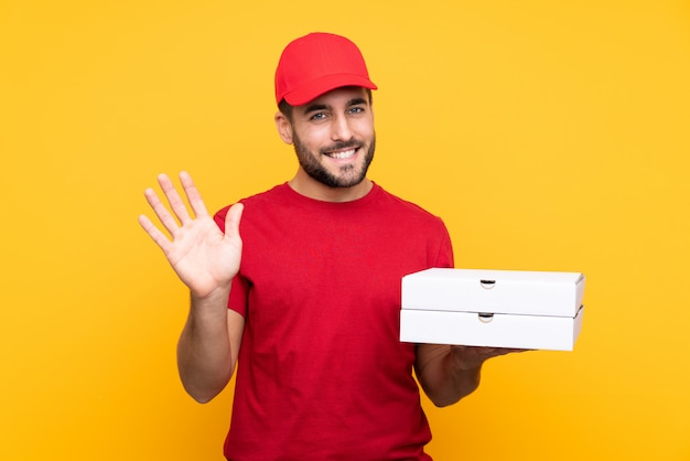 Pizza delivery man with work uniform picking up pizza boxes over isolated yellow saluting with hand with happy expression Premium Photo