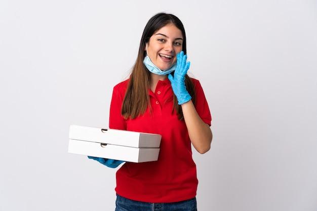 口を大きく開いて白い叫びで分離されたピザを保持しているピザ配達女性 Premium写真
