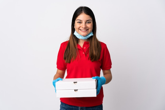 たくさん笑って白で隔離のピザを保持しているピザ配達の女性 Premium写真