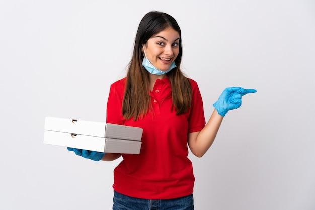 白い壁に隔離されたピザを持って驚いて、人差し指を横に向けてピザ配達の女性 Premium写真