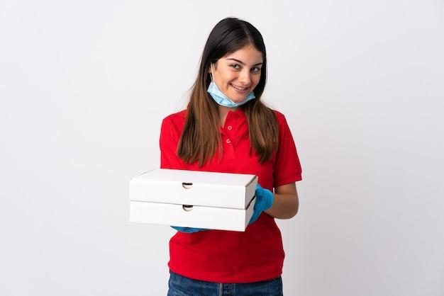 幸せな表情で白い壁に分離されたピザを保持しているピザ配達の女性 Premium写真
