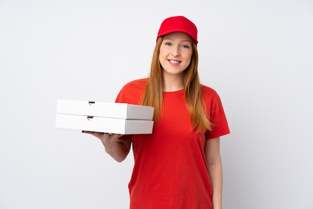 Pizza delivery woman holding a pizza over isolated pink wall smiling a lot Premium Photo
