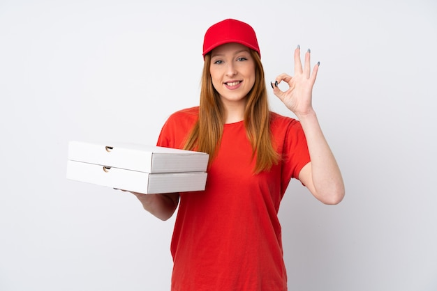 Pizza delivery woman holding a pizza over pink wall showing ok sign with fingers Premium Photo