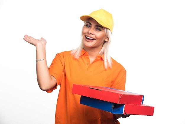 흰색 바탕에 그녀의 손을 보여주는 피자를 들고 피자 배달 여자. 고품질 사진 무료 사진