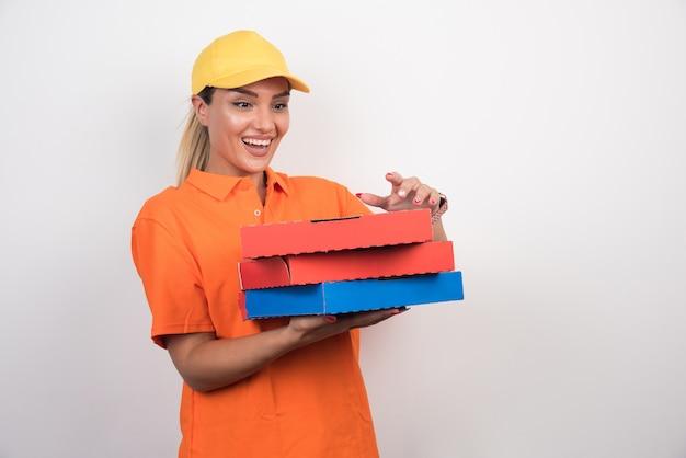 白いスペースに幸せそうな顔でピザボックスを開こうとしているピザ配達の女性 無料写真