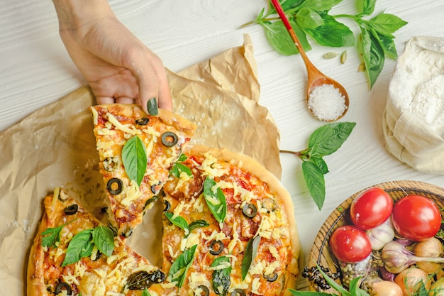 Pizza and hand close up over white background Premium Photo