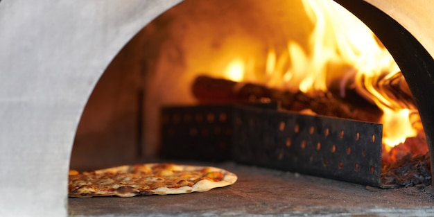 Pizza in hot firewood oven for cook Premium Photo