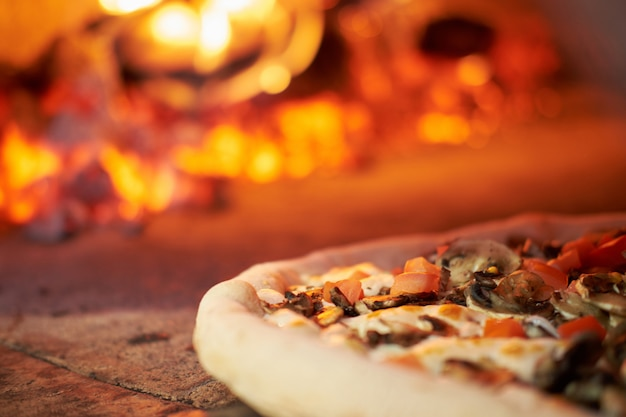Pizza is cooked in the brick oven in pizzeria Premium Photo