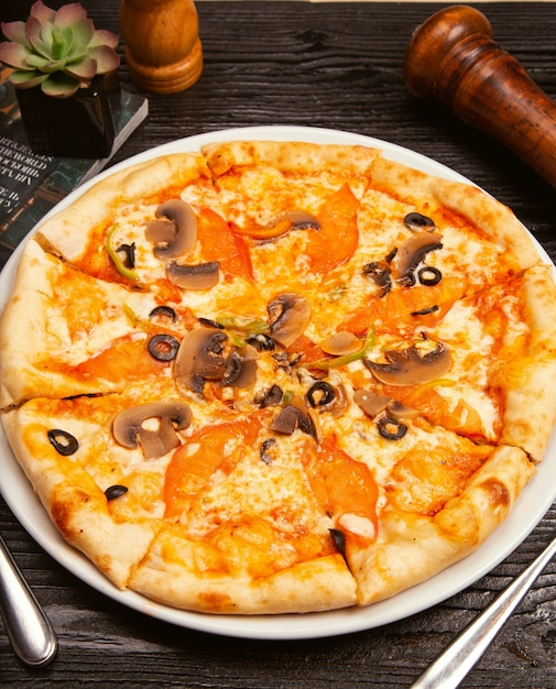 Pizza margarita with black olives, mushrooms, tomato sauce, tomato slices and parmesan cheese on white plate. Free Photo