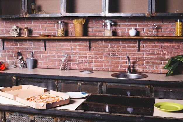 Pizza on empty kitchen Free Photo