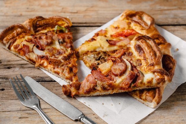 Pizza in the paper box on wooden table Premium Photo