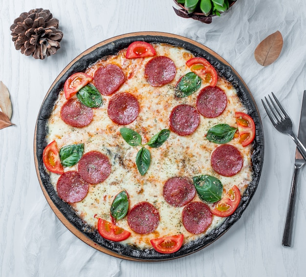 Pizza pepperoni with tomatoes basil and cheese Free Photo