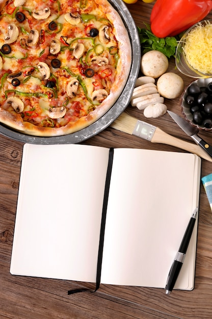 Pizza with blank cookbook and ingredients Free Photo