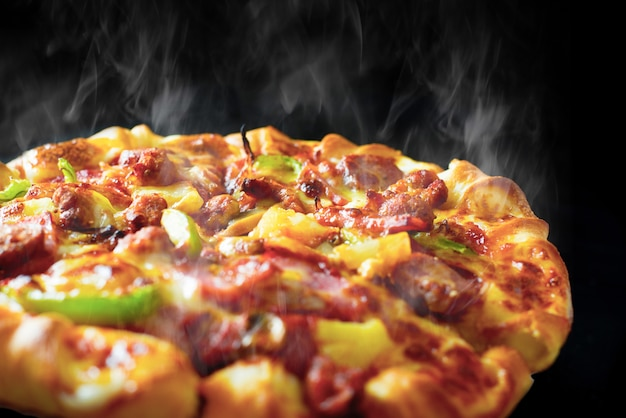 Pizza with cheese ham bacon and pepperoni on isolated black background Premium Photo