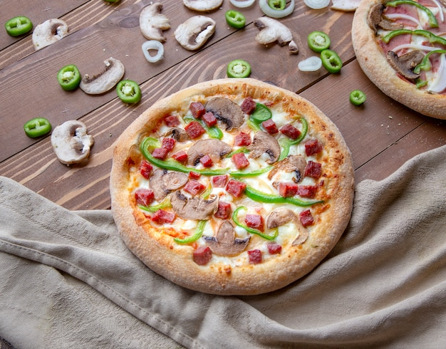 Pizza with chopped sausage, mushrooms and green pepper Free Photo