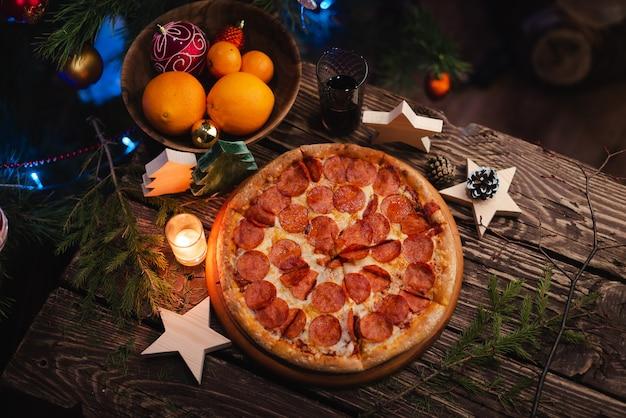 Пицца с рождественскими украшениями на деревянном столе Premium Фотографии