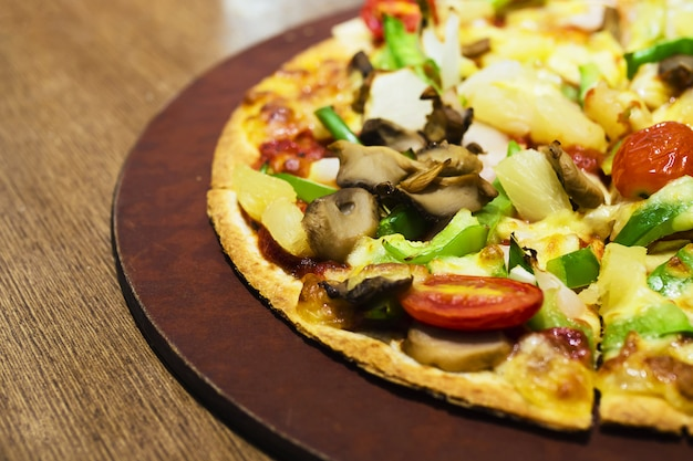 Pizza with colorful vegetable topping ready to be eaten Free Photo