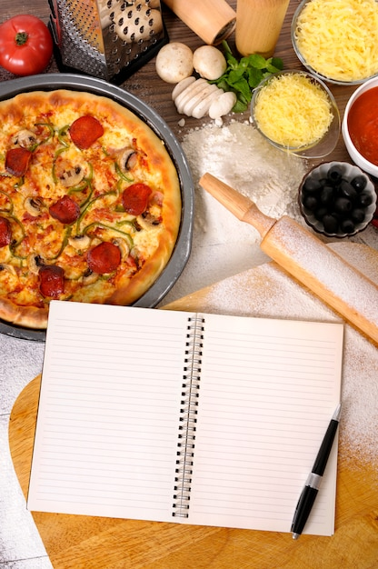 Pizza with cookbook and various ingredients Free Photo