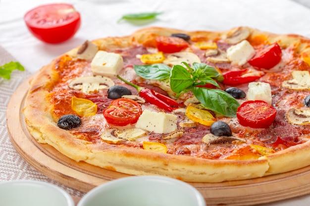 Pizza with mozzarella, ham, cherry tomatoes, black olives Premium Photo
