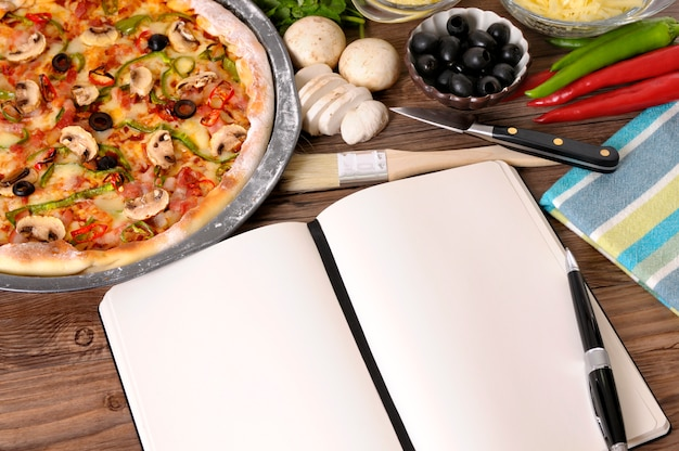Pizza with notebook or cookbook and ingredients Free Photo