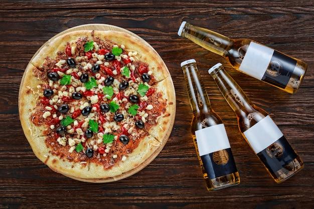 Пицца с оливками, моцареллой и зеленью и три бутылки пива на деревянном фоне. вид сверху. рекламный имидж, баннер Premium Фотографии