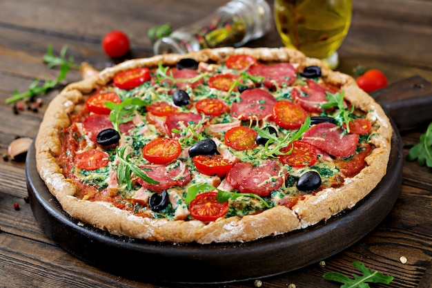 Pizza with salami, tomatoes, olives and cheese on a dough with whole wheat flour. italian food. Premium Photo