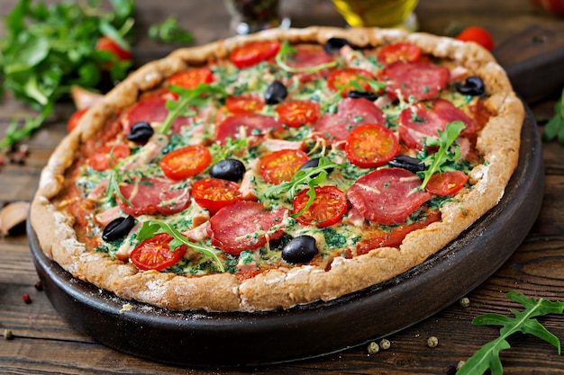 Pizza with salami, tomatoes, olives and cheese on a dough with whole wheat flour. italian food. Free Photo