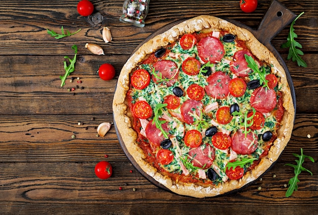 Pizza with salami, tomatoes, olives and cheese on a dough with whole wheat flour.  top vie Premium Photo