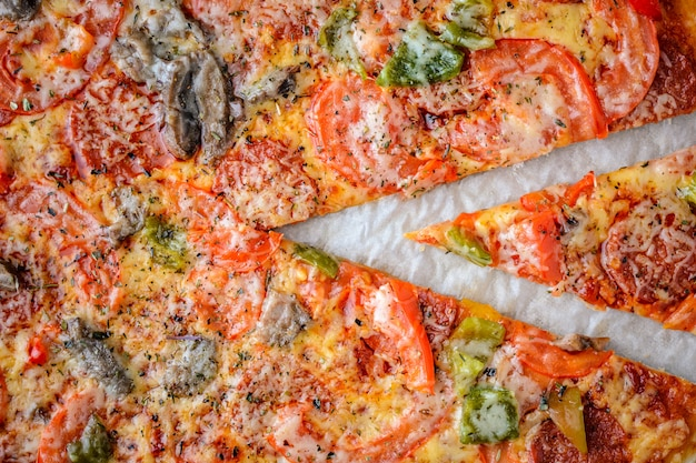 Pizza with salami, tomatoes, pepper and mushrooms is the top view. close-up Premium Photo
