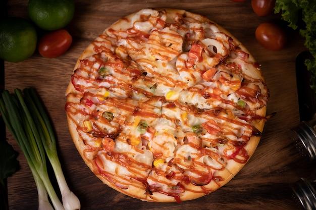 Pizza con salsiccia, mais, fagioli, gamberetti e pancetta su un piatto di legno Foto Gratuite