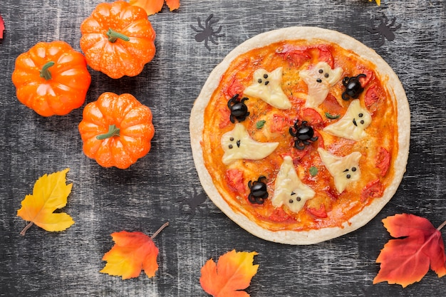 Pizza with scary ghosts on top and pumpkins Free Photo