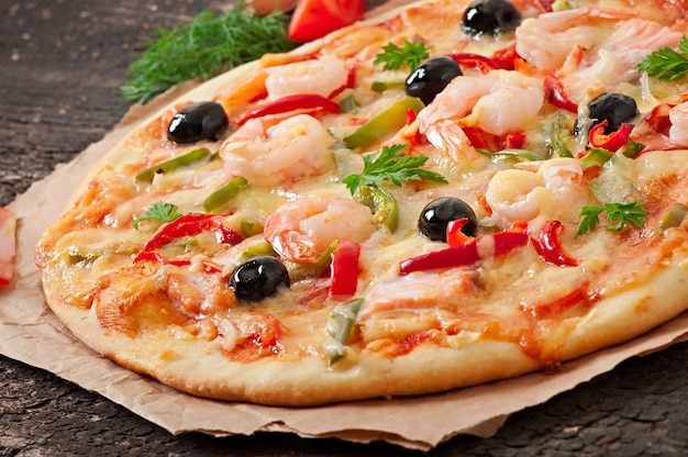 Pizza with shrimp, salmon and olives Free Photo