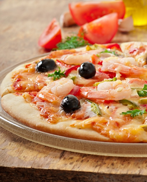 Pizza with shrimp, salmonnd olives Free Photo