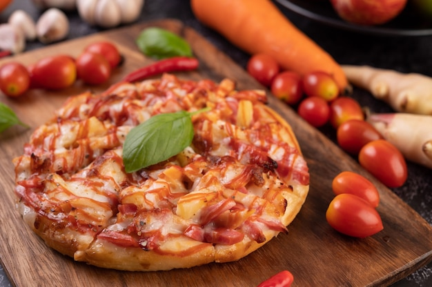 Pizza in a wooden tray with tomatoes chili and basil. Free Photo