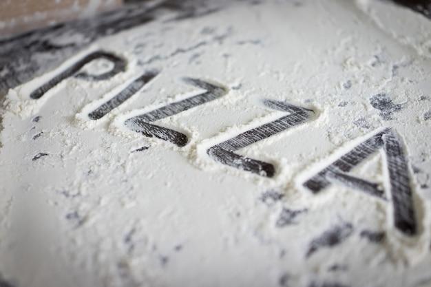 Pizzaの準備ができた生地の書かれた手紙 Premium写真
