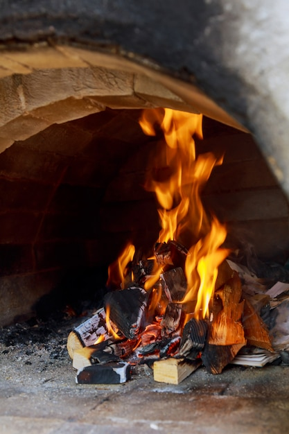 Pizzas baking in an open firewood oven Premium Photo