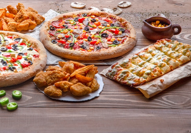 Pizzas, chicken bbq, fried potatoes and cheese rolls on the wooden table Free Photo