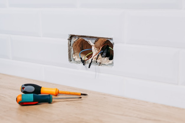Place for installation of power socket with protruding wires and screwdriver. Premium Photo