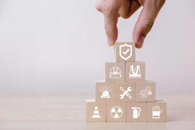 Place wooden blocks on the pyramid. 100 percent work safety concept. Premium Photo