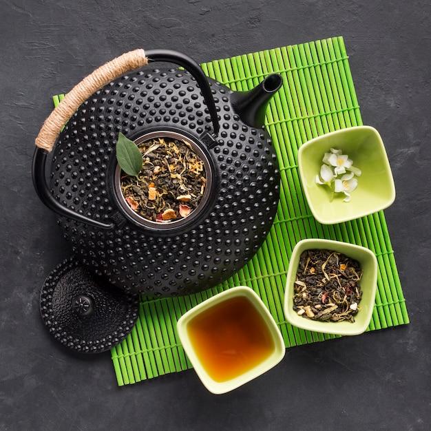 Взгляд высокого угла чайника с высушенной травой и белым цветком жасмина на зеленом placemat Бесплатные Фотографии