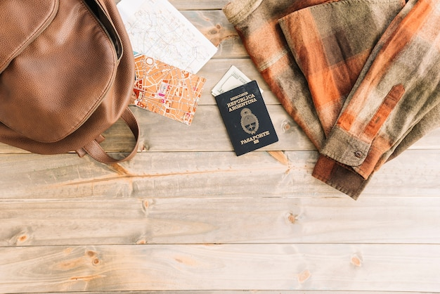 Plaid shirt; bag; map; passport and currency on wooden backdrop Free Photo